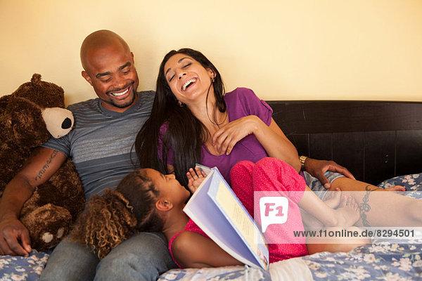 Mutter und Vater mit Tochter auf dem Sofa  lachend