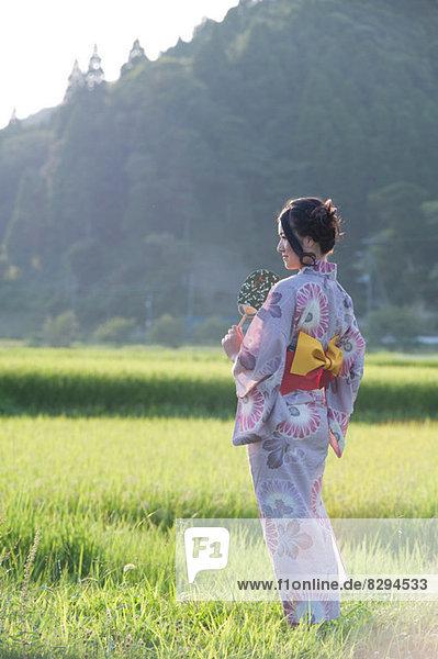 Junge Japanerin mit Kimono auf der Wiese