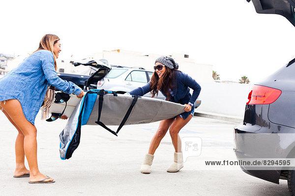 Weibliche Freunde ziehen Deckung vom Surfbrett.