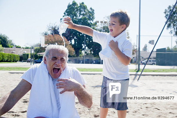Junge gießt Wasser auf Großvater