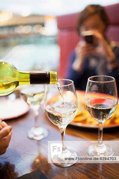 Woman pouring white wine  close up