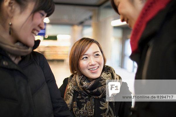 Drei junge asiatische Frauen im Gespräch