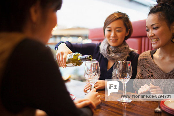 Young woman pouring wine in restaurant