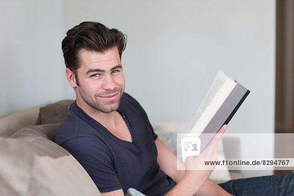 Man looking up from book