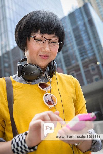 Junge Frau in gelbem Top mit mp3-Player