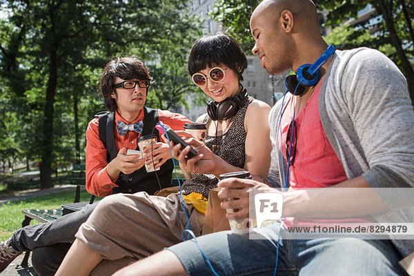 Three friends in park with mp3 player