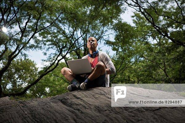 Junger Mann auf Felsen sitzend mit Laptop