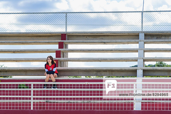 USA  Texas  American High School Girl in Sports Outfit sitzend ganz allein auf Stadiontribünen