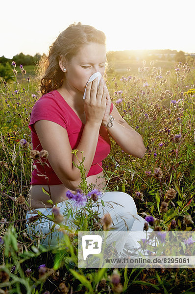 young pregnant woman with hay fever kneeling in a flower meadow