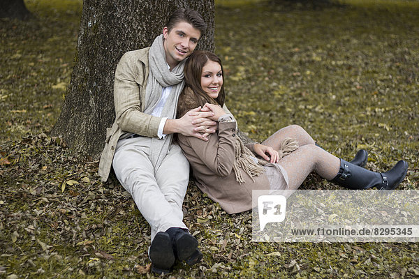 Happy couple in a park sitting at a tree