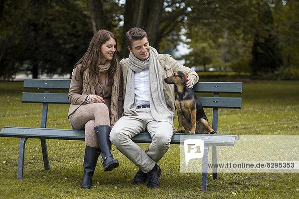 Glückliches Paar mit Hund im Park