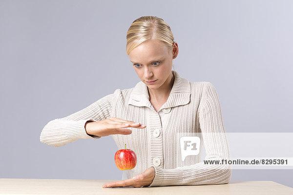 Junge Frau beim Anblick des fliegenden Apfels