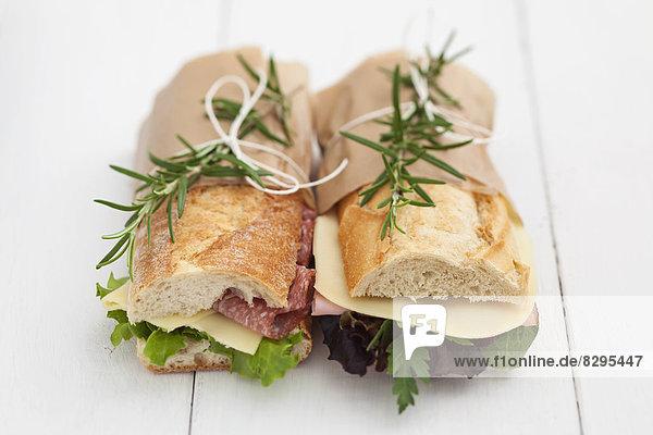 Baguette-Sandwiches mit Rosmarin auf weißen Holzbrettern