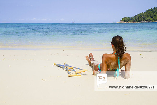 Thailand  Koh Surin island  woman with crutches lying at the white sandy beach