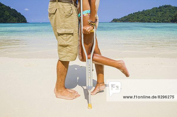 Thailand  Insel Koh Surin  Frau mit Krücken küssender Mann am weißen Sandstrand