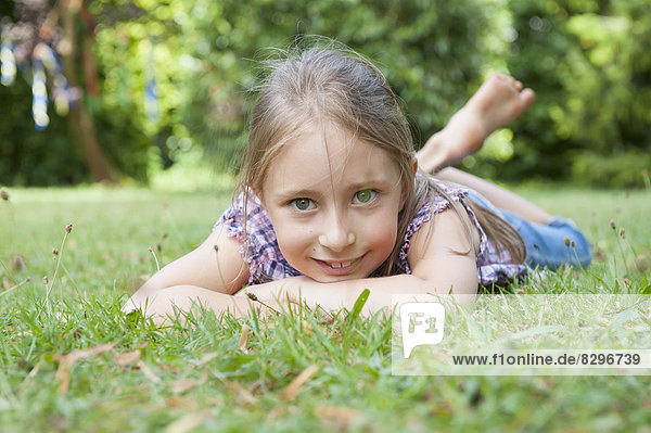 Smiling girl lying in grass