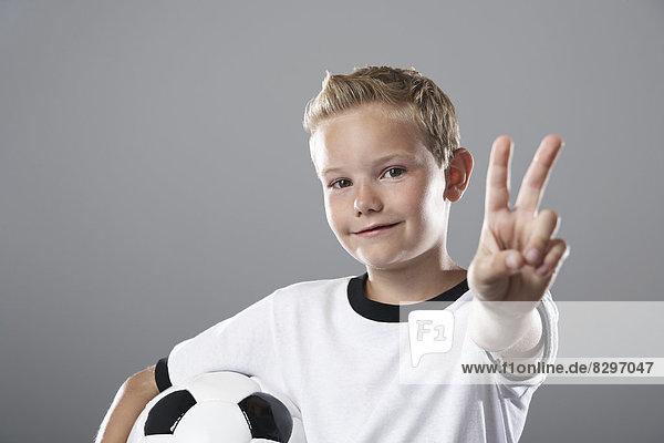 Junge im Fußballtrikot mit Siegeszeichen Junge im Fußballtrikot mit Siegeszeichen