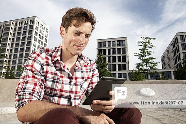 Junger Mann mit E-Book im Freien