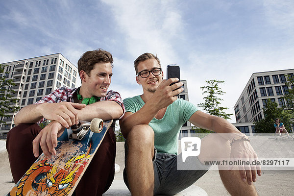 Germany  Bavaria  Munich  Two friends with skateboard and smartphone