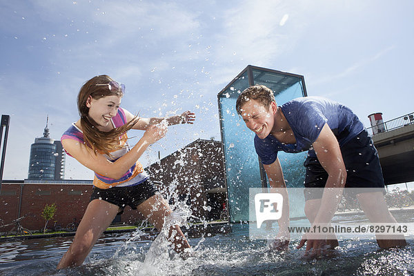 Germany  Bavaria  Munich  Couple splashing with water at fountain