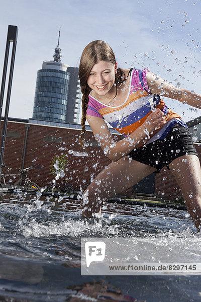 Junge Frau spritzt mit Wasser am Brunnen