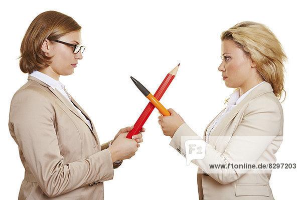 Zwei Geschäftsfrauen kämpfen mit Bleistiften