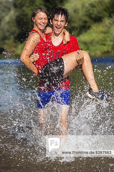 sportlicher junger Mann mit junger Frau beim Laufen durch den Rems-Fluss