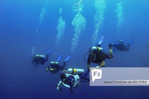 Scuba divers with air bubbles