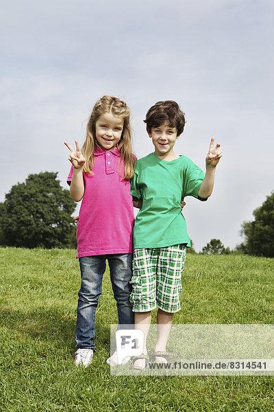 Junge und Mädchen posieren auf einer Wiese Junge und Mädchen posieren auf einer Wiese