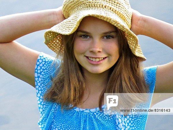 Young girl holding her straw hat