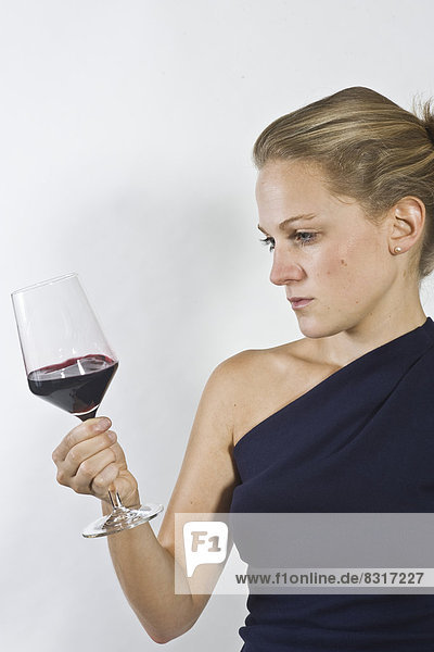 Young woman examining glass of red wine