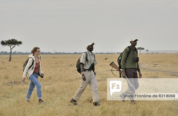 Tourist with armed guard and guide on a walking safari