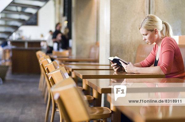 Junge Frau liest ein Buch in einem Restaurant