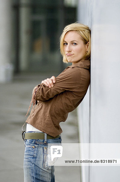 Young woman leaning against concrete wall