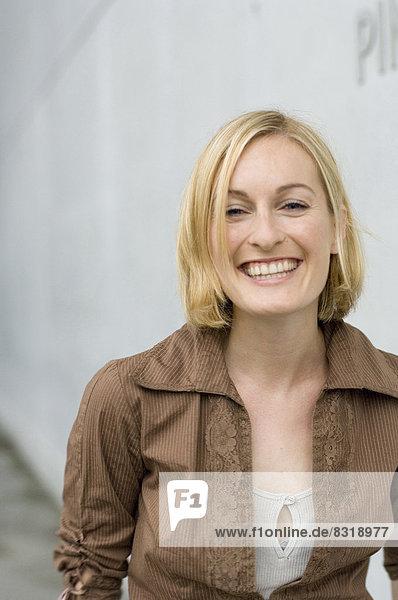 Fröhliche junge Frau in brauner Bluse