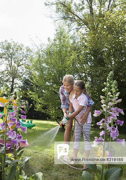 Mother and daughter in garden watering flowers