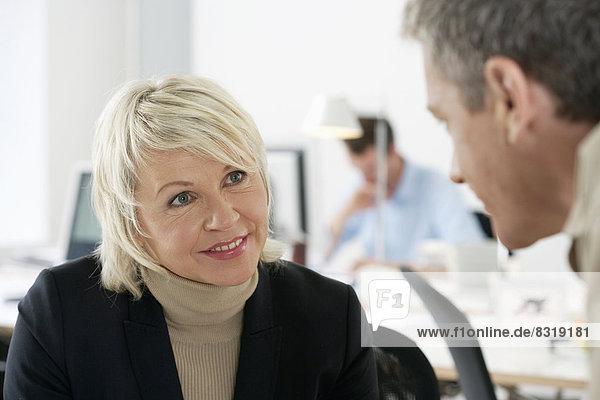 Geschäftsmann und Geschäftsfrau unterhalten sich im Büro
