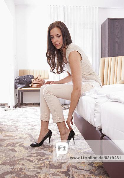 Frau im Hotelzimmer zieht Schuhe an