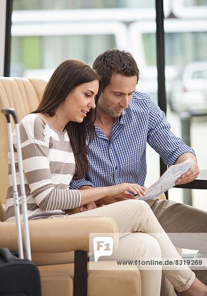 Paar sitzt in Hotellobby mit Stadtplan