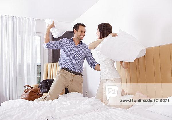 Paar bei einer Kissenschlacht im Hotelzimmer