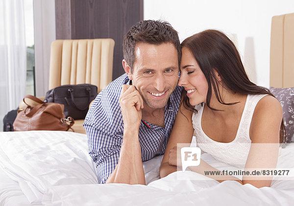 Paar liegt verliebt auf dem Bett im Hotelzimmer