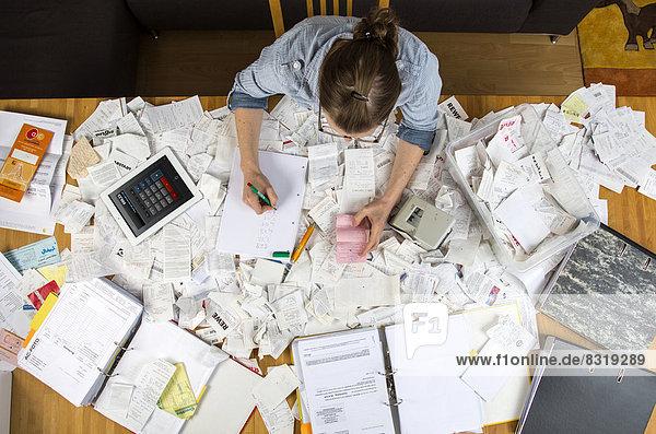 Frau mit Belegen  Unterlagen  Rechnungen und Kassenbons für die Steuererklärung