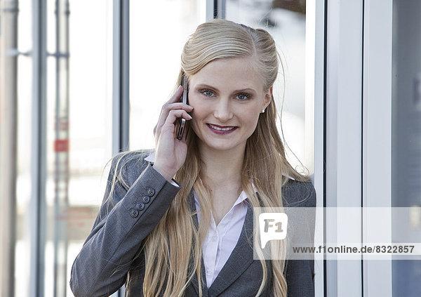 Lächelnde Geschäftsfrau telefoniert mit Handy  Porträt