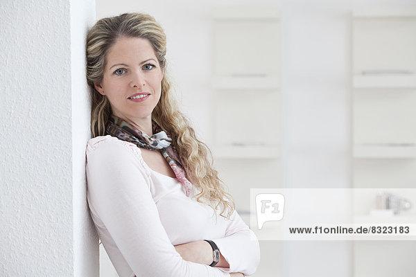 Lächelnde blonde Frau lehnt an einer Wand  Porträt