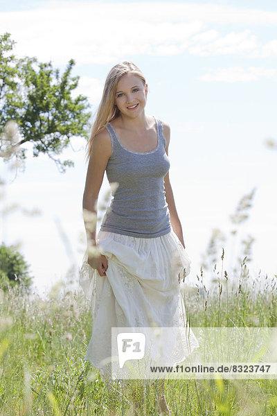 Attraktive blonde junge Frau steht in einem Feld