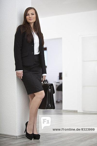 Junge brünette Geschäftsfrau lächelt