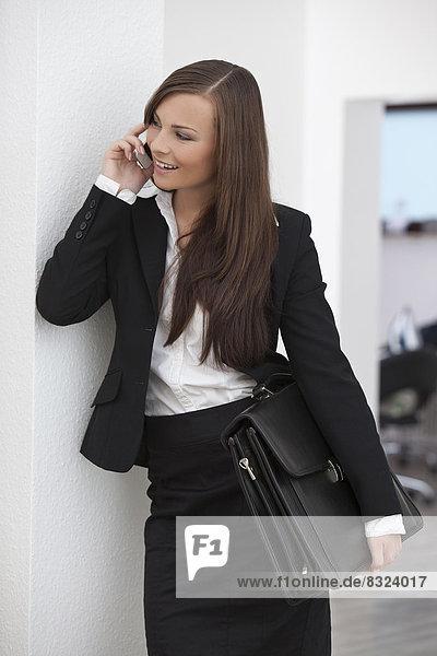 Junge brünette Geschäftsfrau telefoniert mit Handy