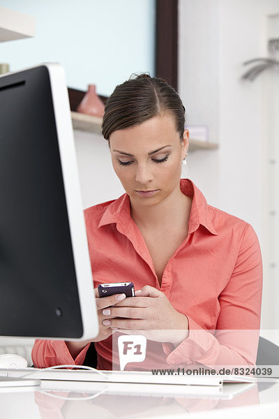 Young brunette businesswoman at desk with cell phone and computer