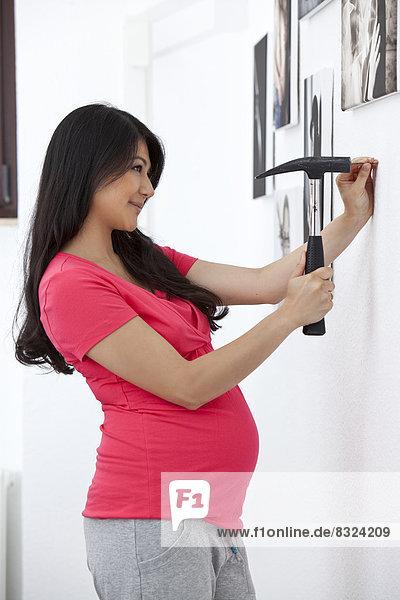 Schwangere Frau hämmert an einer Wand