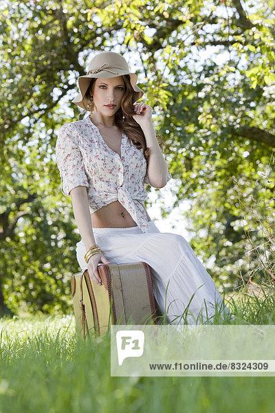 Brünette junge Frau mit Koffer auf einem Feld